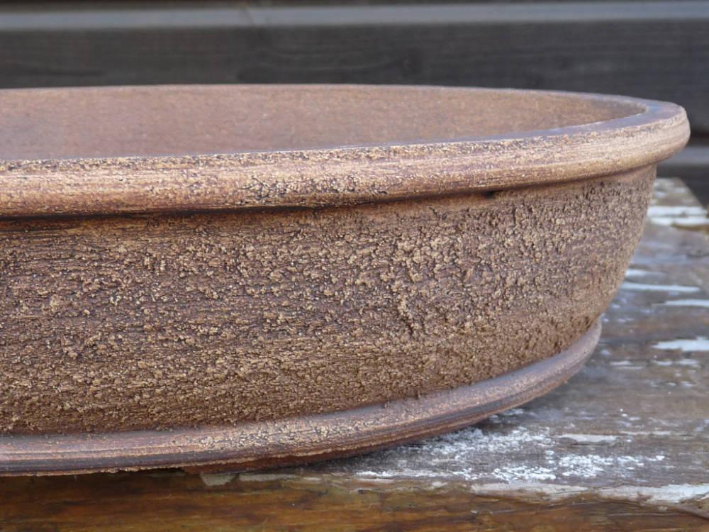 Texture avec du grain sur une poterie bonsai ovale
